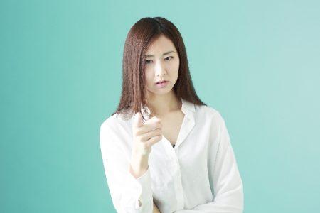 指をさして指摘する女性